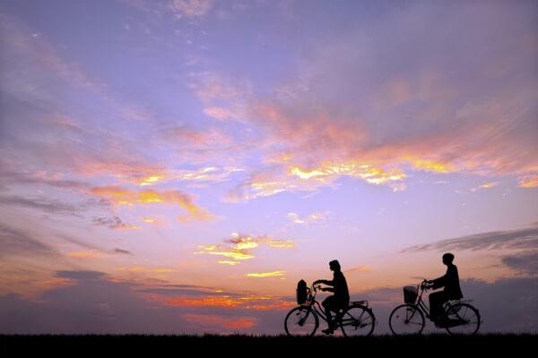 夕陽を背景に自転車通学する男女のシルエット