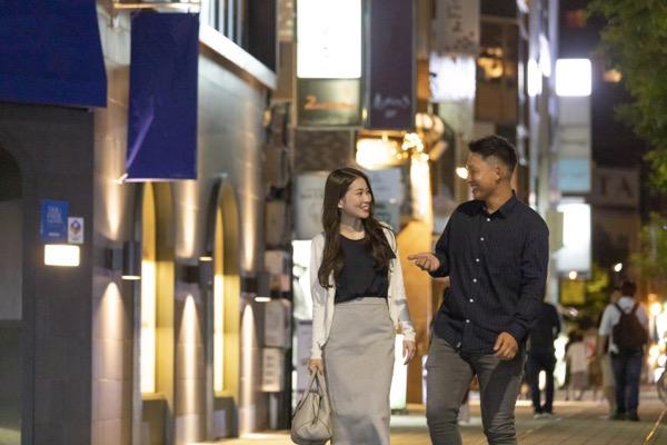 夜の繁華街を楽しそうに歩く若い男女
