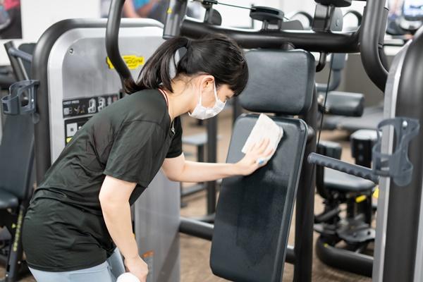 トレーニング後のマシンを消毒する女性